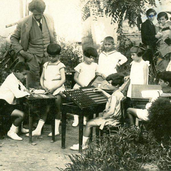 Α' τάξη Προτύπου, Ιούνιος 1928. Ομάδα παιδιών του Προτύπου εργάζεται στο ύπαιθρο. Ο Μίλτος Κουντουράς, η Αλεξάνδρα Κεσσανλή και τελειόφοιτες του Διδασκαλείου παρακολουθούν την εργασία των παιδιών.