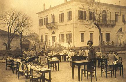 1930, η Α' τάξη του Προτύπου με φόντο το Διδασκαλείο. Δασκάλα η Αλεξάνδρα Κεσσανλή.